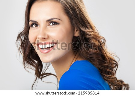 Portrait of young cheerful smiling woman, over grey  - stock photo