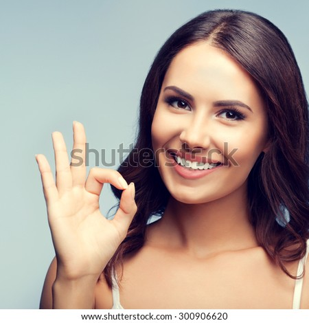 Portrait of young cheerful smiling woman showing okay gesture in white tank top clothing - stock photo