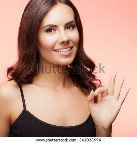 Portrait of young cheerful smiling woman showing okay gesture, over light red background - stock photo