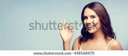 Portrait of young cheerful smiling woman showing okay gesture, with blank copyspace area for text or slogan - stock photo