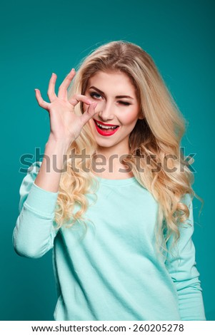 Portrait of young cheerful smiling woman showing okay gesture, with copyspace, - stock photo