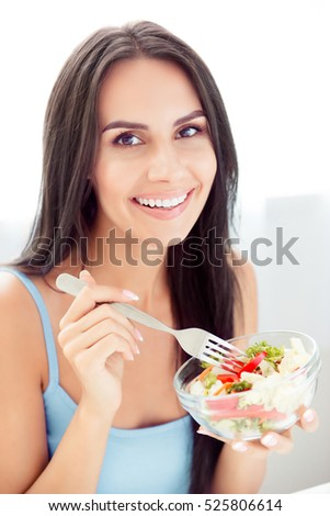 Portrait of young cheerful woman eating a healthy salad.