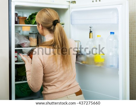 Portrait of young cheerful woman near filled fridge indoors - stock photo