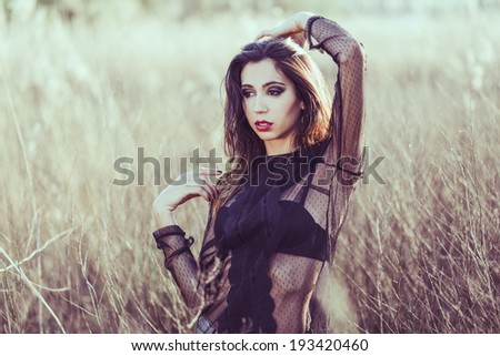 Portrait of young cheerful woman on golden cereal field in spring  - stock photo