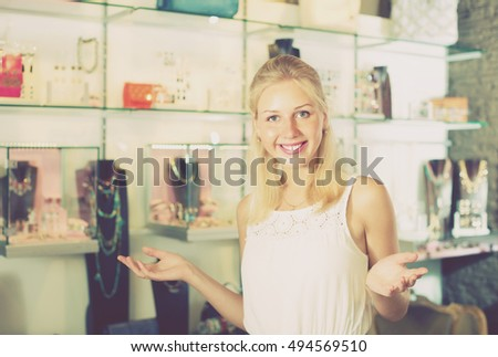 portrait of young cheerful woman standing among showcases in shop with bijouterie