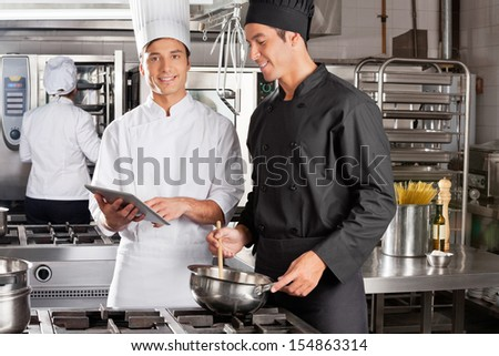 Portrait of young chef assisting colleague in preparing food at kitchen - stock photo