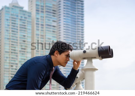 Portrait of young chinese business man standing in Panama City and looking through binoculars. Concept of forecasting, career, success - stock photo
