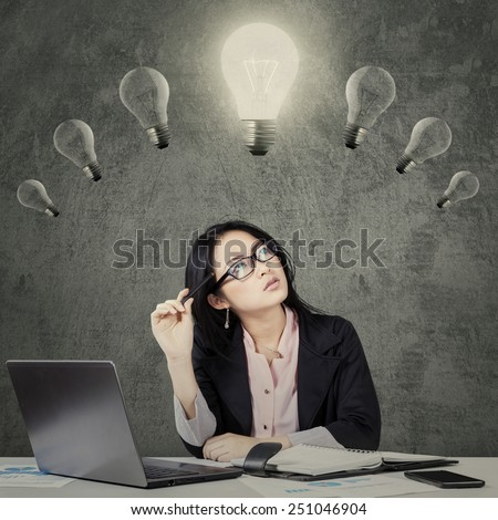 Portrait of young chinese businesswoman thinking an idea while looking at lightbulb over head - stock photo