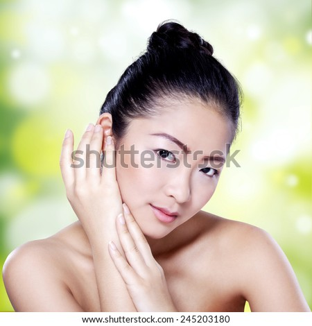 Portrait of young chinese girl with beauty perfect skin looking at the camera against bokeh light background - stock photo