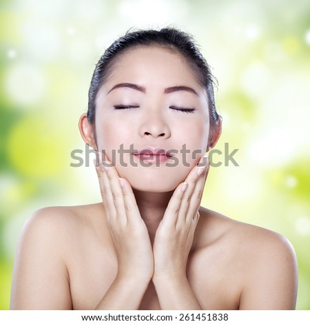 Portrait of young chinese girl with soft beauty skin touching her face against bokeh light background - stock photo