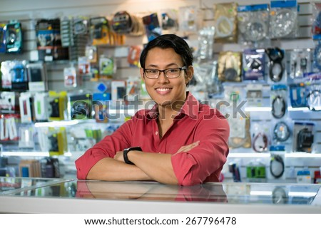 Portrait of young chinese man working as clerk in computer and technology store, smiling at camera and leaning on desk in shop - stock photo