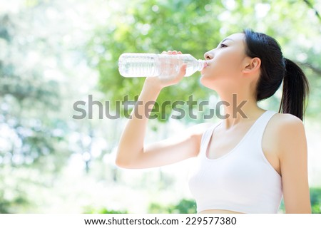 portrait of young chinese woman drinking water after jogging - stock photo