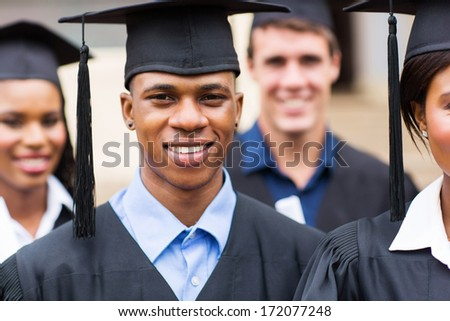 portrait of young college graduates in graduation gown - stock photo