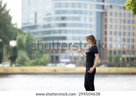 Portrait of young confident business woman using cellphone app, messaging on the street in front of blue glass modern office building in the city beside river bank, profile view - stock photo