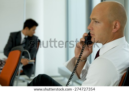 portrait of young confident caucasian businessman talking on phone - stock photo
