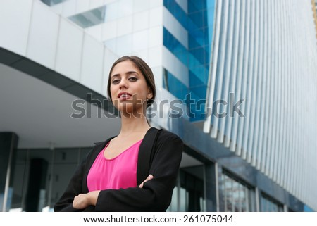 Portrait of young confident hispanic business person with arms crossed, looking at camera and smiling - stock photo