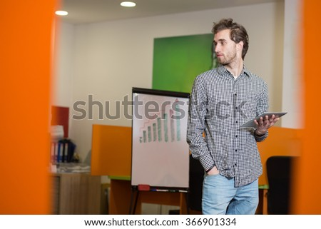Portrait of young confident men employee dressed in casual clothes working on digital tablet while standing in modern office space, successful male entrepreneur in suit using touch pad during break - stock photo