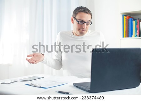 Portrait of young confused man using laptop - stock photo