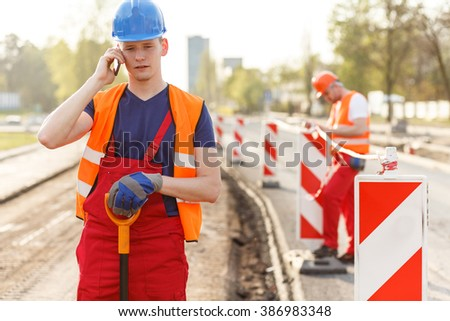 Portrait of young construction worker talking on the phone - stock photo