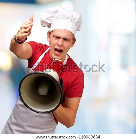 portrait of young cook man screaming with megaphone and gesturing against a nature background - stock photo