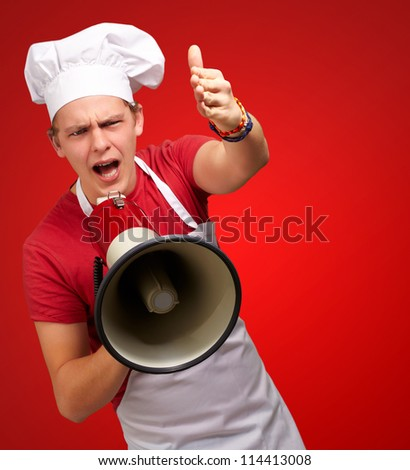 portrait of young cook man screaming with megaphone and gesturing over red background