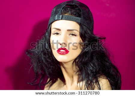 Portrait of young cool sexy sensual beautiful bad girl with brunette curly hair red glossy lips and black cap looking forward on bright pink studio background, horizontal picture - stock photo