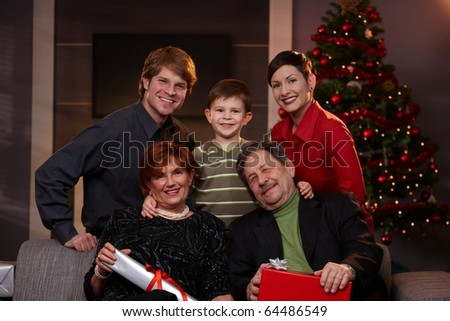 Portrait of young couple and son with grandparents at christmas, smiling. ? - stock photo
