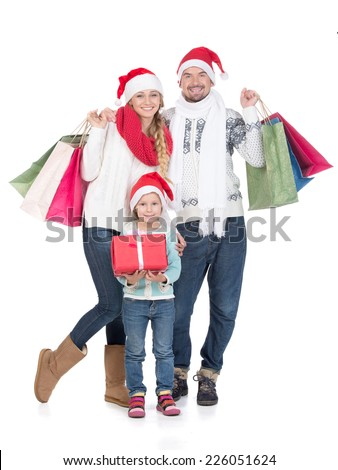 Portrait of young couple and their daughter in Santa caps looking at camera. Isolated on white background. - stock photo