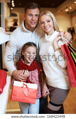 Portrait of young couple and their daughter looking at camera in the mall - stock photo