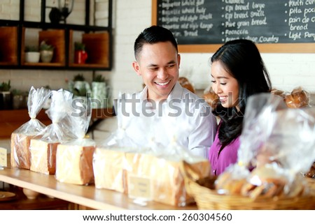 portrait of young couple at bakery shop - stock photo