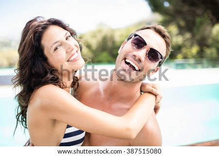 Portrait of young couple cuddling each other near pool at sunny day - stock photo
