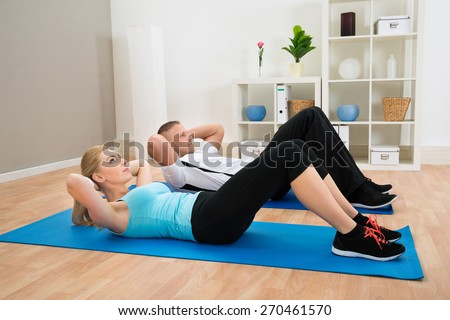 Portrait Of Young Couple Doing Crunches On Exercising Mat - stock photo