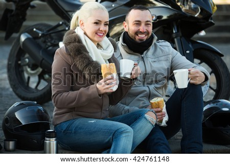 Portrait of young couple drinking coffee and chatting near motorcycle - stock photo