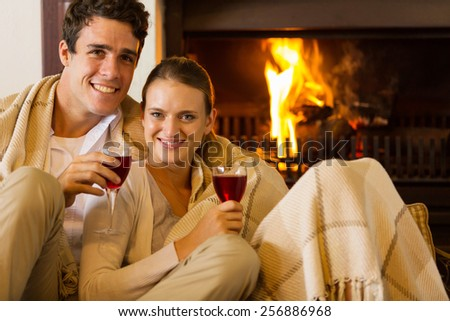 portrait of young couple drinking red wine in front of fireplace - stock photo