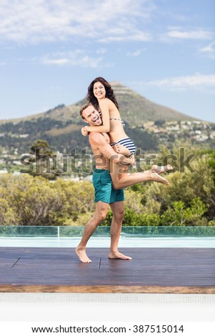 Portrait of young couple enjoying near pool on a sunny day - stock photo