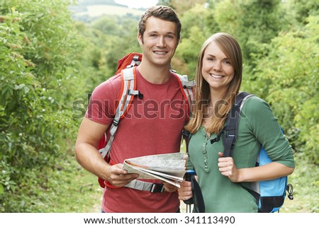 Portrait Of Young Couple Hiking In Countryside - stock photo