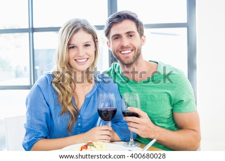 Portrait of young couple holding a wine glass at home - stock photo