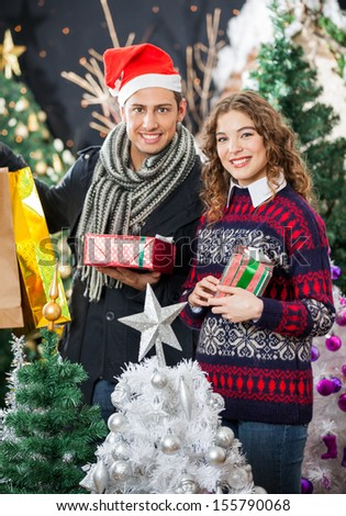Portrait of young couple holding Christmas presents and shopping bags at store - stock photo