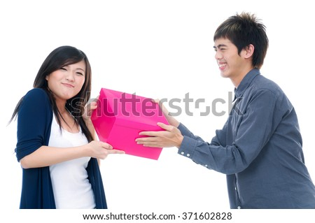 Portrait of young couple holding red gift box - stock photo