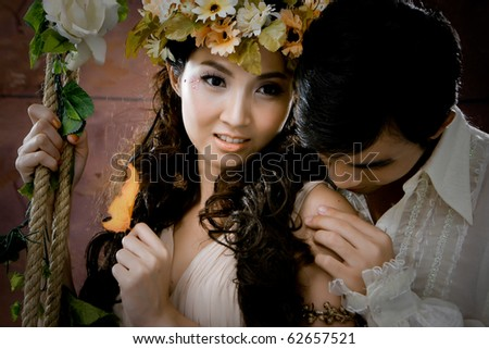 Portrait of young couple in antique dress in erotic emotion - stock photo