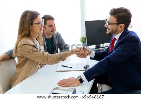 Portrait of young couple in bank office shaking hand to financial adviser.