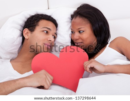 Portrait Of Young Couple In Bed Holding Heart - stock photo