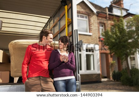 Portrait of young couple in front of new home with sold sign - stock photo