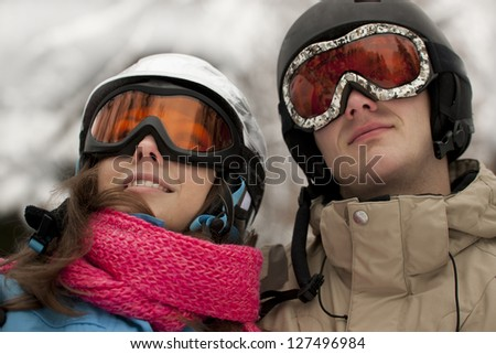 Portrait of young couple in helmets and gogles looking up - stock photo