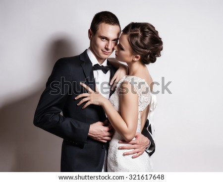 Portrait of young couple in love posing at studio dressed in classic clothes - stock photo