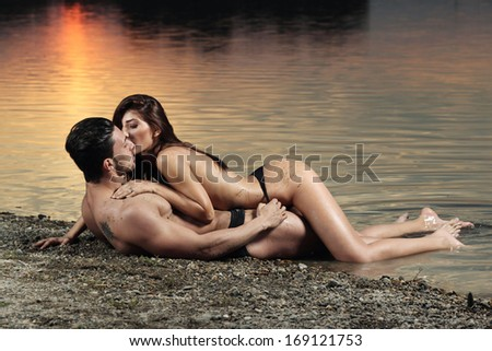 Portrait of young couple in love posing on the beach. Fashion color.