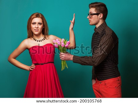 Portrait of young couple in love with flowers tulips posing at studio dressed in classic clothes - stock photo
