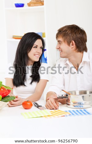 portrait of young couple in their kitchen happy smile, looking to each other - stock photo