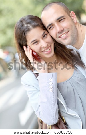 Portrait of young couple in town with smartphone