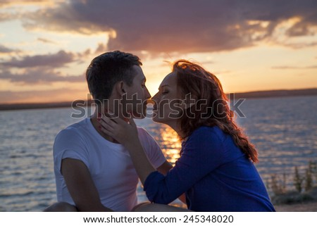 Portrait of Young couple kissing at sunset sky with dramatic clouds Redhead Woman hand lie on brunette man neck Nails with red manicure Lips Pair near each other Sun reflection on water sea texture  - stock photo